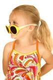 Sid den bärande solglasögon för galen blond flicka att le för sikt Arkivbilder