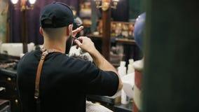 Sid och dra tillbaka sikten av den stilfulla barberaren med skägget som utför en frisyr med sax som rymmer en hårborste i hans hä stock video