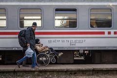 Refugees, men and a woman in wheelchair, boarding a train to cross the Croatia Serbia border at Sid train station on Balkans Route stock images