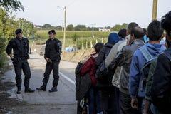 Sid, Serbie - 3 octobre 2015 : Policiers croates observant des réfugiés franchir la frontière serbo-croate Photographie stock libre de droits