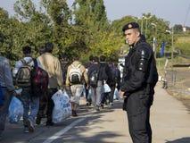 Sid, Serbie - 3 octobre 2015 : Policiers croates observant des réfugiés franchir la frontière serbo-croate entre les villes du Si Image stock