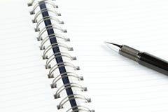 Sida av anteckningsboken med den svarta pennan royaltyfri foto