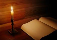 Sida av den gamla boken som är upplyst med stearinljuset royaltyfri bild