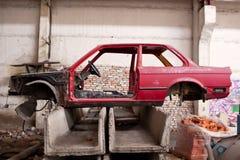 Sida av den kraschade röda bilen Arkivbild
