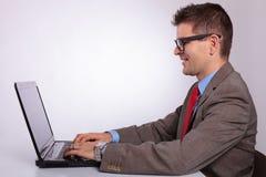 Sida av den unga affärsmannen som arbetar på bärbara datorn arkivbild