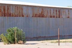 Sida av en delvist rostad metallbyggnad fotografering för bildbyråer