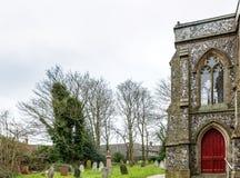 Sida av en kyrka i mitt av en kyrkogård i England Royaltyfria Foton