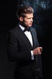 Sida av en modeman i smoking som röker en cigarr Arkivfoto
