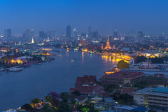Sida för Bangkok cityscapeflod på skymning som kan se watarun Royaltyfri Bild