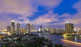 Sida för flod för byggnad för Bangkok cityscape modern på skymningtid, Th Arkivfoton
