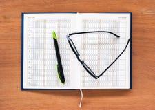 Sida för kalender för dagbokstadsplanerarebok öppen med exponeringsglas och pennan Arkivbild