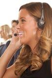 Sida för leende för kontorskvinnahörlurar med mikrofon Royaltyfri Fotografi