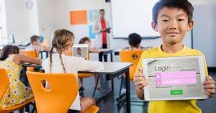 Sida för skolpojkevisninginloggning på apparaten i klassrum royaltyfri foto