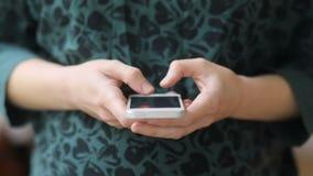 Sida-sikt av unga gravida kvinnor i retro noiresweatshot för grön tappning med sötsakanbudhud som knackar lätt på hennes smartpho stock video