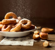 Sida som är nära upp på en grupp av nya hemlagade donuts med socker och det mörka träbakgrundsgolvet royaltyfri foto