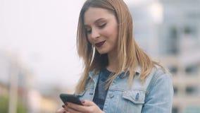 Sida-till-framdel closeup av den ungdomliga attraktiva blonda flickan med mörker - röda mjuka kanter i blå grov bomullstvilldomst arkivfilmer