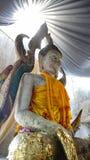 Sidan av Buddhastatyn, som bär guld- kläder, och har ett ljus s Arkivfoto