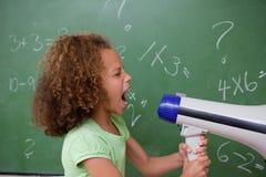 Sidan beskådar av en schoolgirl som skriker till och med en megafon Royaltyfri Bild