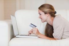 Sidan beskådar av kvinnan på sofaen som direktanslutet shoppar Arkivbild