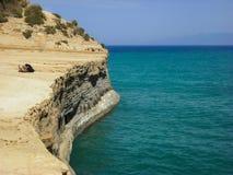 Sidari, Corfu, Greece - rocky cliff with backpacks and beautiful turquoise water.  Stock Photography