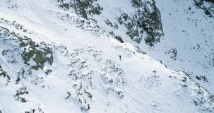 Side aerial over winter snowy mountain with mountaineering skier people walking up climbing.snow covered mountains top. And ice glacier.Winter wild nature stock footage