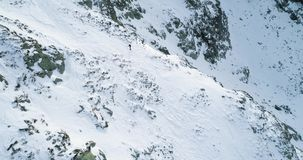 Side aerial over winter snowy mountain with mountaineering skier people walking up climbing.snow covered mountains top. And ice glacier.Winter wild nature stock video