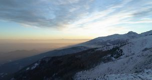 Side aerial top view over winter snowy mountain and woods forest at sunset or sunrise.Blue hour dusk or dawn twilight. Alps mountains snow season establisher.4k stock footage