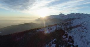 Side aerial top view over winter snowy mountain and woods forest at sunset or sunrise.Dusk or dawn twilight sunshine stock video