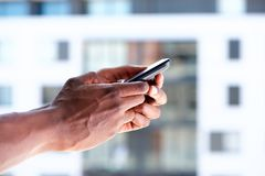 African male hands holding mobile phone. Side of african male hands holding mobile phone Royalty Free Stock Photo