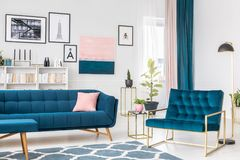 Side angle of living room. Side angle of blue living room interior with pink and golden accents royalty free stock image