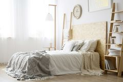 Side angle of white bed. With wooden bedhead and gray blanket in bright bedroom Stock Photography