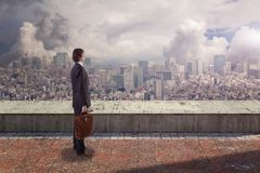 Side back view of a businessman on rooftop looking at city with copy space. royalty free stock image