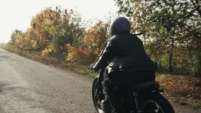Side and back view of a man in black helmet and leather jacket riding motorcycle on a asphalt road in autumn. Trees with