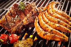 Side of beef next to prawns roasting on grill. Side of beef garnished with rosemary and salt next to prawns and tomatoes roasting on flaming grill Stock Photos