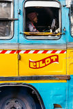 The side of blue bus with driver on the street in Kolkata, India. Stock Photography