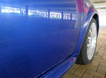 Side of blue sports car. Close up of door and tire of blue sports car parked in a garage Royalty Free Stock Photography