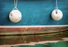 Side of Boat with Buoys. Two round buoys hang from a side of a fishing boat in an Oregon harbor, with the boat reflecting on the water creating a colorful Stock Images
