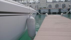 Side of a Boat. Side view of an empty white boat using for transportation of divers with multiple buffer buoys on the sides stock footage
