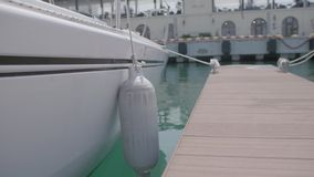Side of a Boat. Side view of an empty white boat using for transportation of divers with multiple buffer buoys on the sides stock video footage