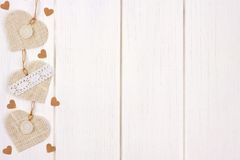 Side border of burlap hearts over rustic white wood Stock Photography