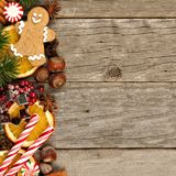 Side border of Christmas decor and treats over rustic wood Stock Photography