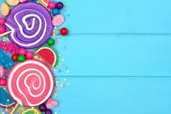 Side border of colorful assorted candies against blue wood Royalty Free Stock Photos