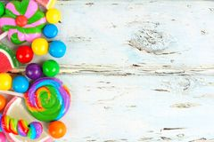 Side border of colorful candies against rustic wood. Side border of varied colorful candies against a rustic wooden background Stock Images