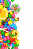 Side border of colorful candies over white. Side border of an assortment of colorful candies against a white background Royalty Free Stock Photo