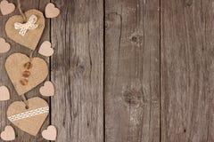 Side border of handmade burlap heart decorations over rustic wood Stock Photos