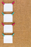 Side border of neatly hanging blank notepads. Side border of neatly hanging blank white square notepads on colorful wooden clothespins over a rustic hessian or royalty free stock image