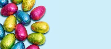 Free Side Border Of Colorful Wrapped Chocolate Easter Eggs On Blue Background. Top View. Royalty Free Stock Photos - 214650778