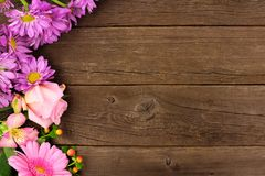 Side border of pink and purple flowers against a rustic wood background. Side border of pink and purple flowers with rose, daisies and lilies against a rustic Stock Photo