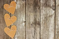 Side border of rustic heart shaped gift tags against wood Stock Photos
