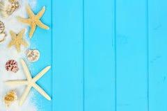 Side border of sand, seashells and starfish on blue wood